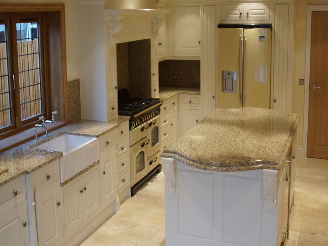 Handcrafted kitchen with granite worktops and travertine flooring.